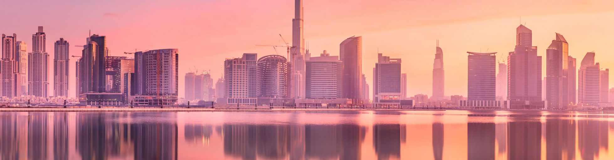 Cityscape of Dubai and panoramic view of Business bay with reflection of skyscrapers on water during purple sunrise, UAE
